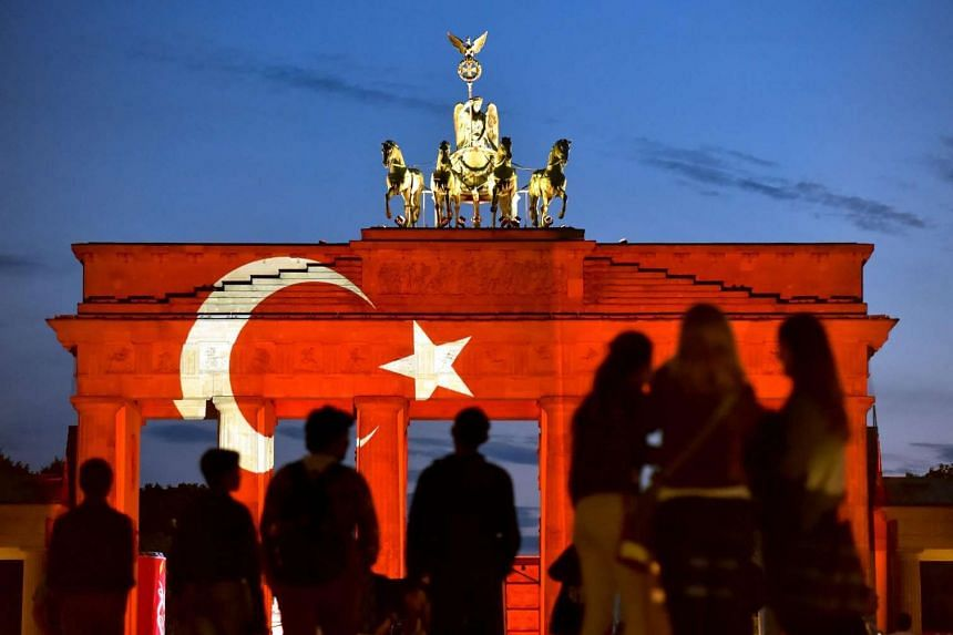 People look at the Brandenburg Gate onto which a Turkish flag is projected in Berlin, Germany, on June 29.