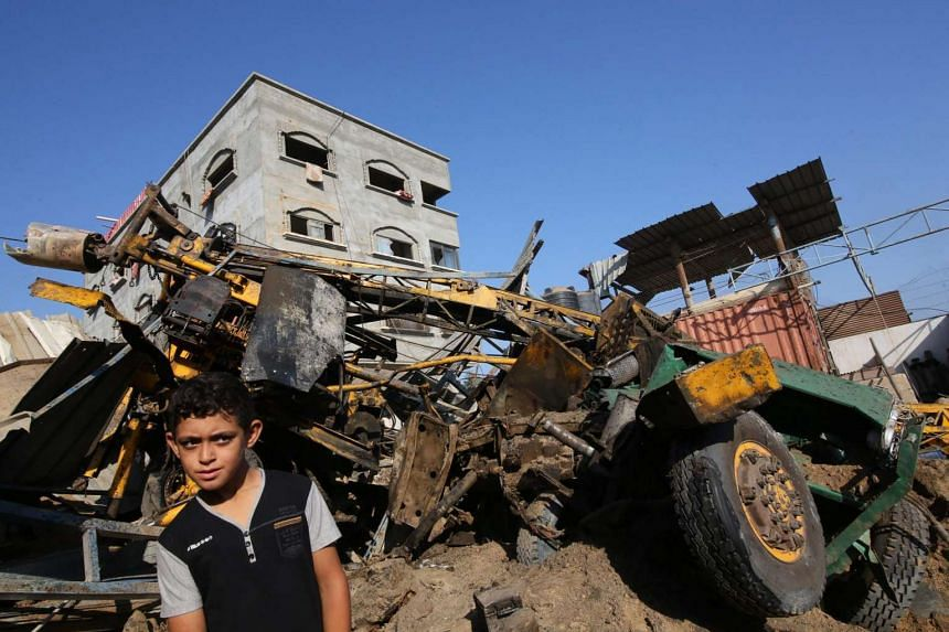 A Palestinian boy looks at the damage following an airstrike by Isreali Defense Forces on a workshop in Gaza City, July 2.