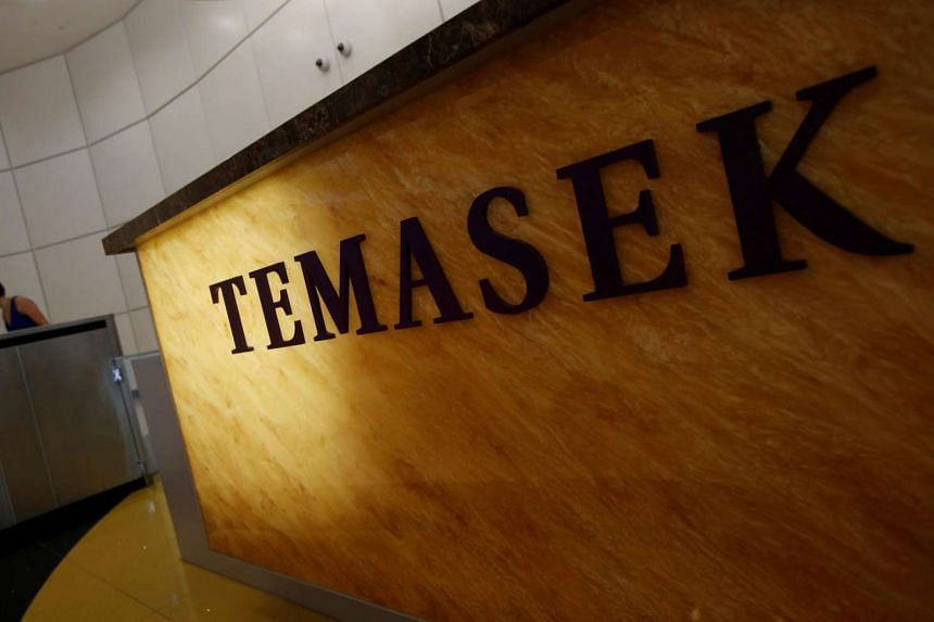 A woman passes a logo of state investor Temasek Holdings at their office in Singapore on July 8.