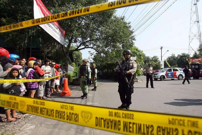 Indonesian police officers stand guard after a suicide bomb attack at the Police Headquarters in Solo, Central Java, Indonesia, on July 5.