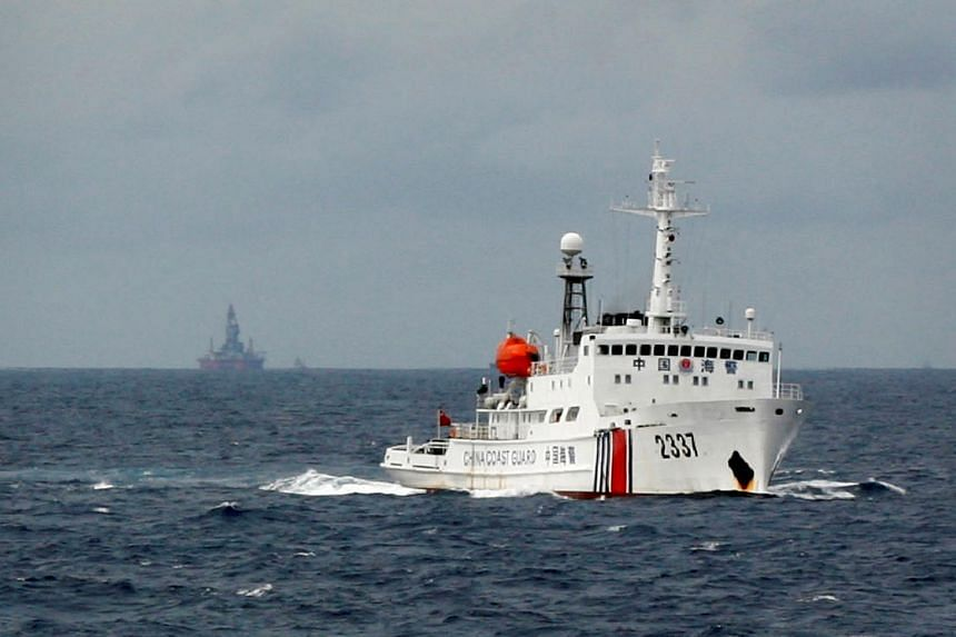 A Chinese Coast Guard vessel (right) passes near the Chinese oil rig Haiyang Shi You 981 (left) in the South China Sea in 2014.