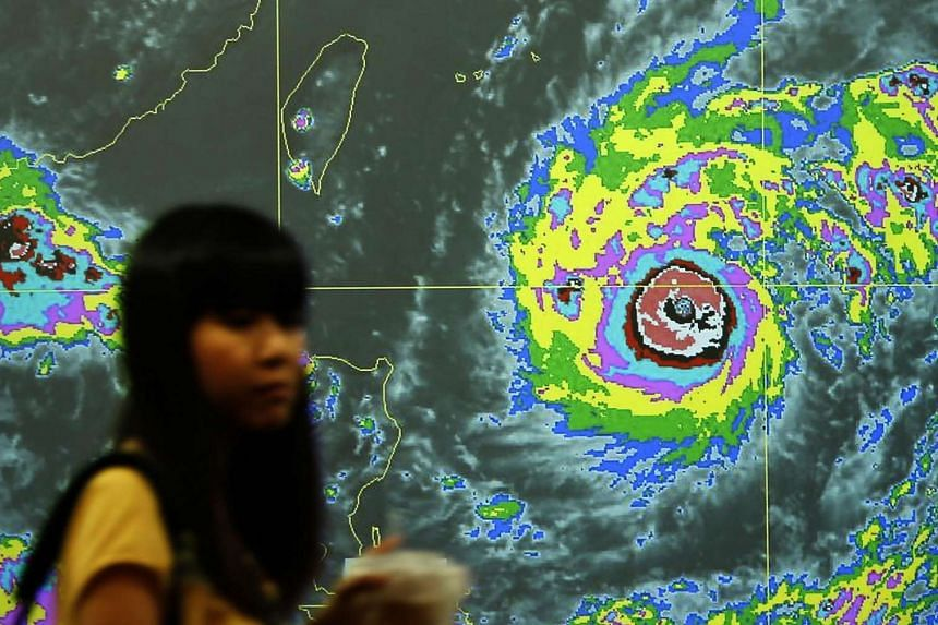 A Taiwanese walks past a video screen with the graph of Typhoon Nepartak heading towards Taiwan.