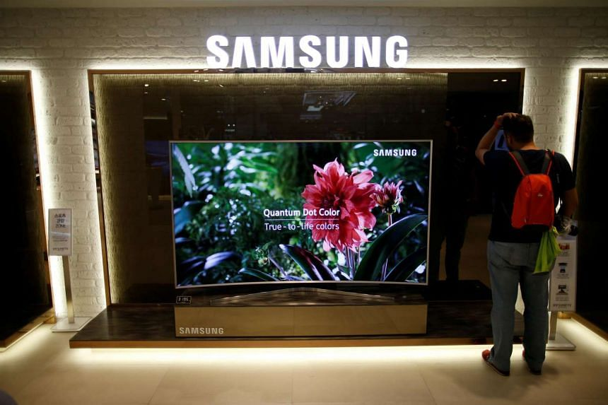 A man stands next to a Samsung Electronics Quantum Dot SUHD television at its headquarters in Seoul, South Korea, on July 4.