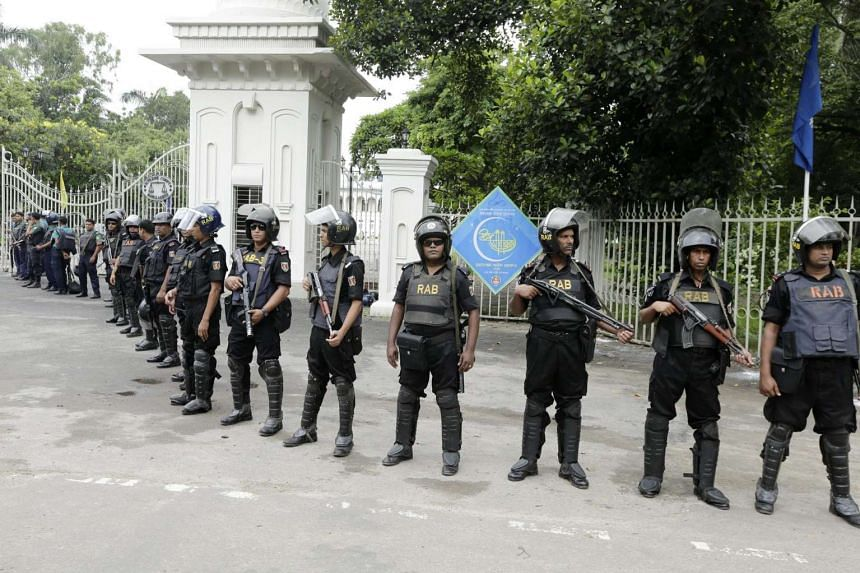 Security officials stand guard as Muslims offer prayers in the National Eid Prayer Ground at the High-Court in Dhaka, Bangladesh, on July 7.