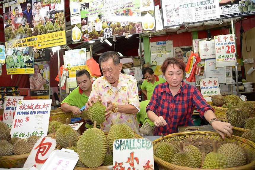 """Madam Ang together with her father at their durian stall in Balestier Road. While prices have increased, she says customers will still buy the fruit if they """"crave for it"""". Dry weather in Malaysia and Thailand has decreased durian harvests, and the p"""