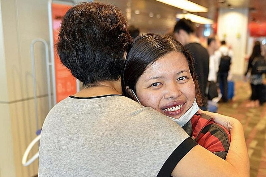 Ms Titin hugging her employer at the airport yesterday. She is grateful to her as well as members of the public who donated $22,000 that helped her pay the medical bills, which came to more than $25,000.
