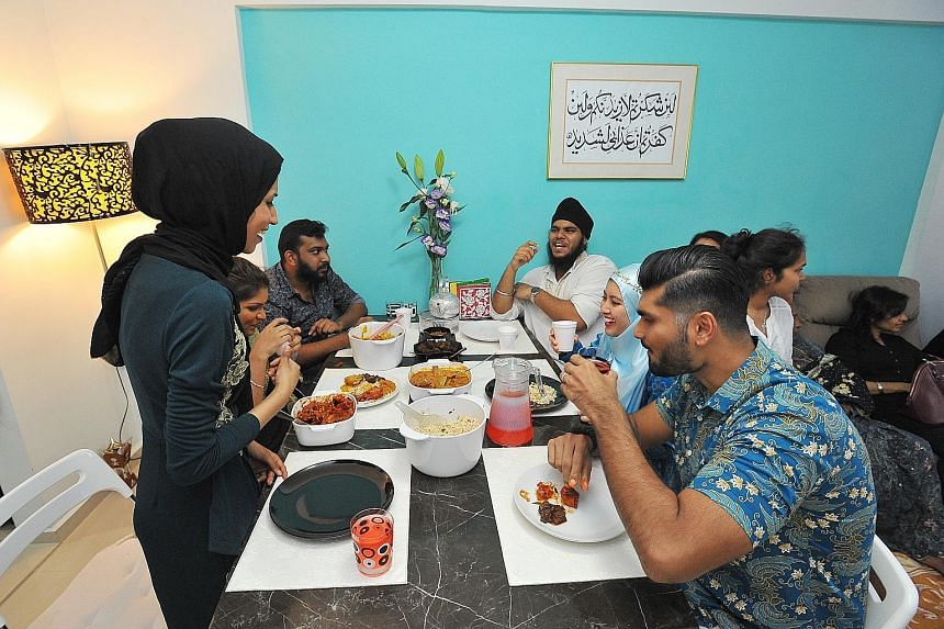 Flight attendant Noor Mastura (far left), 26, invited guests of other faiths into her home yesterday to experience Hari Raya Aidilfitri festivities and share a meal with her family members. She hosted copywriter Sumalatha Navanesan, 26, a Hindu; adve