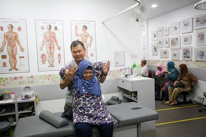 TCM therapist Lam Kean Lung treating Madam Kamisah at a Sian Chay Medical Institution clinic in Geylang. The 62-year-old, who was suffering from frozen shoulder pains, could raise her arms again after two sessions. Sian Chay has grown from one clinic