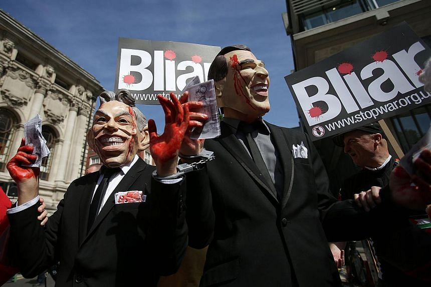 Demonstrators wearing masks depicting former British Prime Minister Tony Blair (left) and former US President George W. Bush protesting in London yesterday as they awaited the outcome of the Iraq War Inquiry. Sir John Chilcot, who led the seven-year