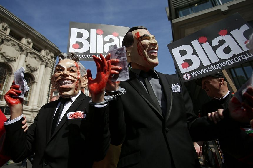 Demonstrators wearing masks depicting former British Prime Minister Tony Blair (left) and former US President George W. Bush protest in London on July 6.