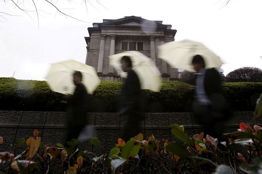 Pedestrians holding umbrellas walk in front of the Bank of Japan headquarters in Tokyo, Japan, January 29.