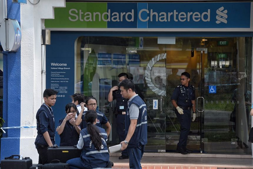 Police officers investigating the scene of a robbery at an outlet of Standard Chartered bank, in Holland Village, on July 7, 2016.