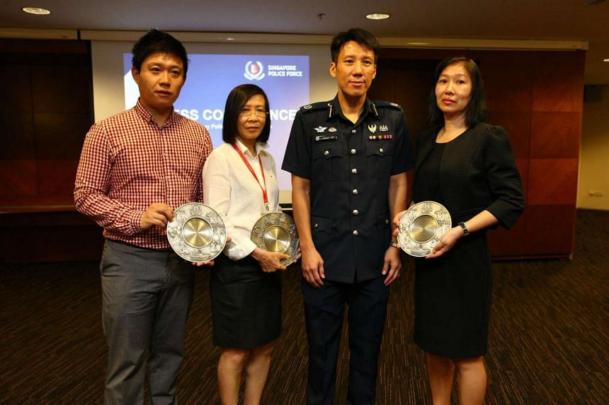 Commander of Central Division, Deputy Assistant Commissioner of Police Arthur Law (second from right) with Hanshan Money Express staff (from left) Li Shu, Thng Koon Eng and Clara Ong (who is receiving it on behalf of her colleague Ms Han).