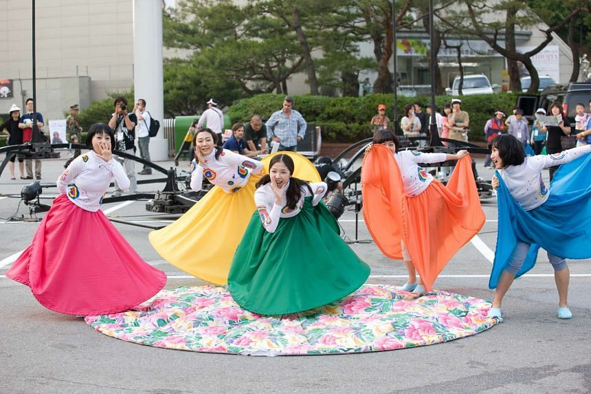 South Koreans in costume performing an outdoor dance.