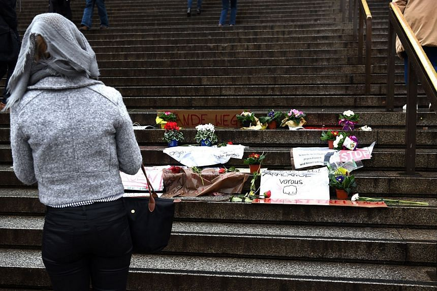A woman looking at flowers and letters of protest, laid down on the steps of the Cathedral in front of the Cologne main train station in Cologne, Germany.