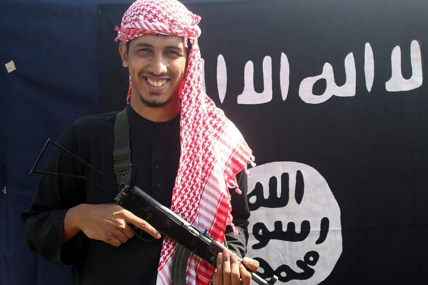 One of the alleged gunmen who carried out the Dhaka attact poses in front of a flag of the Islamic State jihadist group.