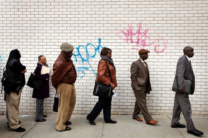 Job seekers stand in line to attend a career fair held by the New York State department of Labour in New York, on April 12, 2012.