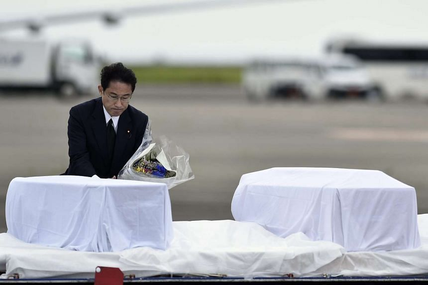 Japanese Foreign Minister Fumio Kishida laying flowers at the caskets of Japanese nationals who were killed in the Dhaka terrorist attack, at Haneda Airport in Tokyo on July 5, 2016.