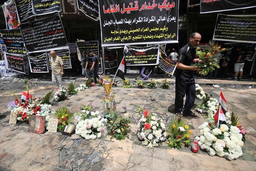 Iraqis laying flowers at the site of a suicide bombing in Baghdad's Karrada district, on July 6, 2016.