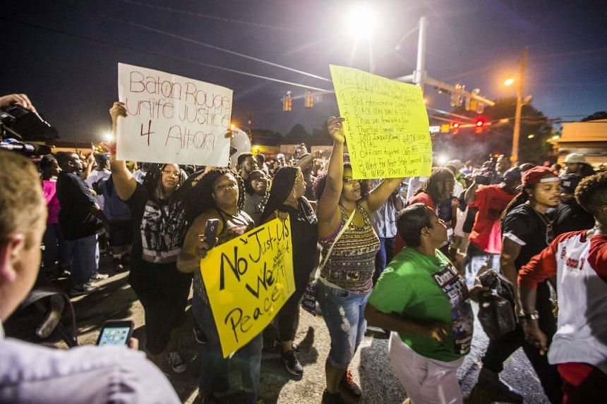 Protesters march to the convenience store where Alton Sterling was shot and killed by an officer, on July 6, 2016, in Baton Rouge, Louisianna.