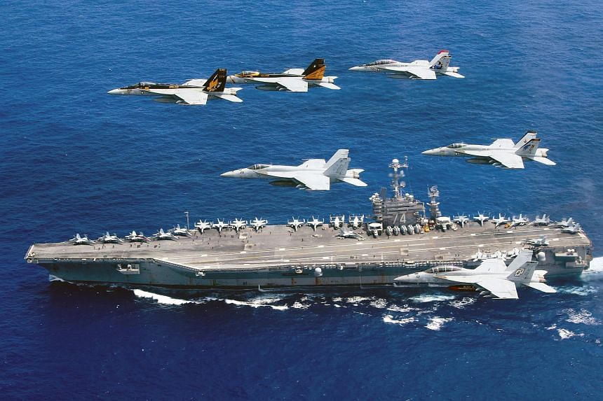 The US Navy shows a flight formation of Boeing F/A-18E and F Super Hornets above aircraft carrier USS John C. Stennis in the Philippine Sea.
