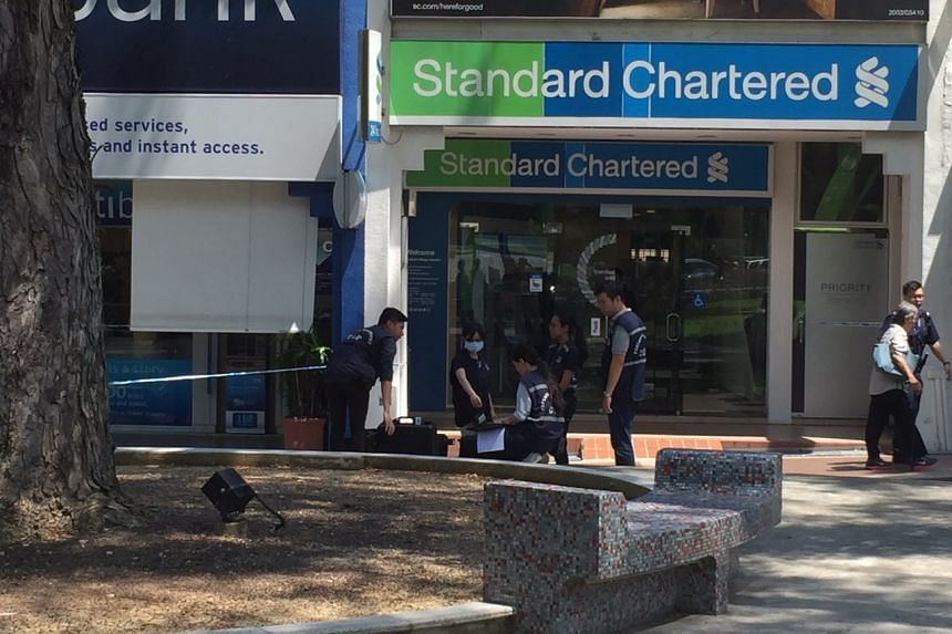 Police seen outside the Standard Chartered bank branch in Holland Village on Thursday (July 7).