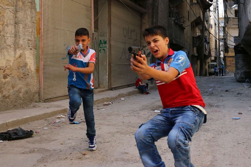 Syrian children play on a street with plastic toy guns in a rebel-held district of the northern city of Aleppo on July 6, 2016.