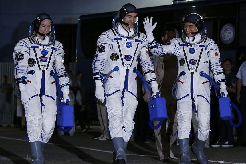 US astronaut Kate Rubins (left), Russian cosmonaut Anatoly Ivanishin (centre) and Japanese astronaut Takuya Onishi walk together as they head to report to the state commission before the boarding of the Soyuz MS-01 spacecraft.