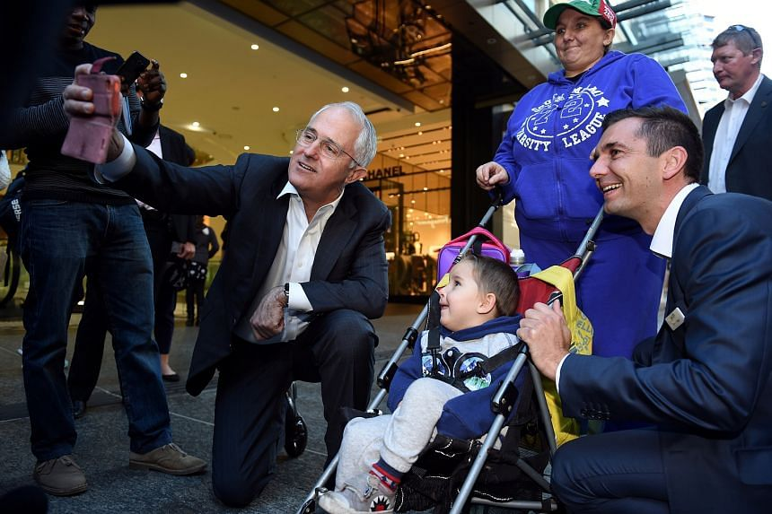 Australian Prime Minister Malcolm Turnbull (left) and member-elect for the Federal seat of Brisbane Trevor Evans (right), pose for a selfie with a woman and child in Brisbane, Australia.