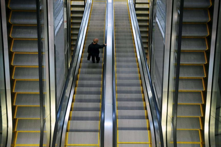 A man takes an escalator at a mall in Singapore on Sept 14, 2011.
