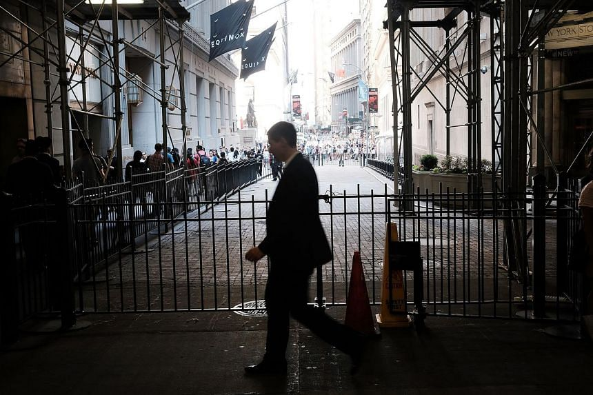 A trader walks out of the New York Stock Exchange on Wall Street on June 24, 2016, in New York City.