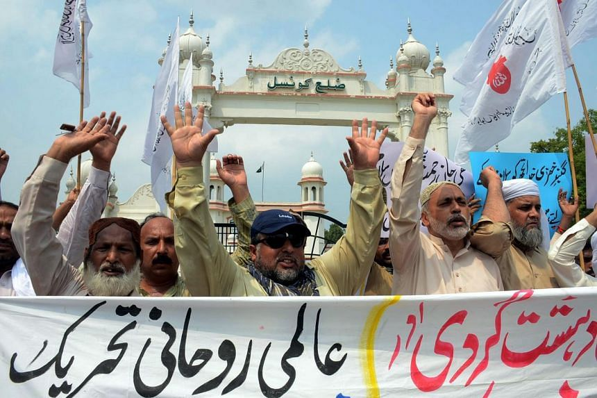 People hold placards and shout slogans against the bombing outside the Prophet Muhammad's Mosque in Madinah, during a protest in Faisalabad, Pakistan, on July 5, 2016.