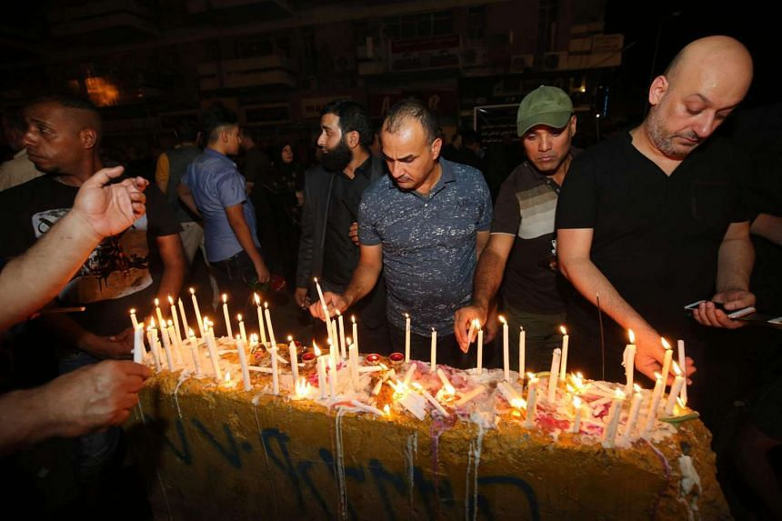 Iraqis light candles on July 5, 2016, at the site of a suicide car bomb attack which took place on July 3 in Baghdad's Karrada neighbourhood.
