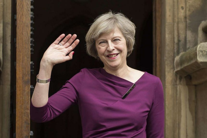 British Home Secretary Theresa May waves to members of the media outside of The Houses of Parliament in London on July 7, 2016.