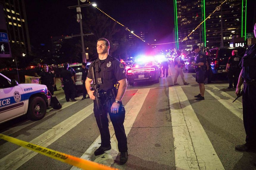 Police officers stand guard at a baracade following the sniper shooting in Dallas, on July 7, 2016.