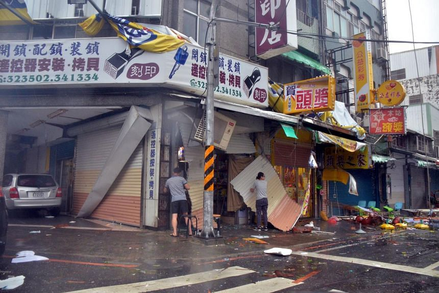 A man and a woman amongst debris in front of a shop with broken shutters, torn away by strong winds of Typhoon Nepartak in Taitung on July 8, 2016.