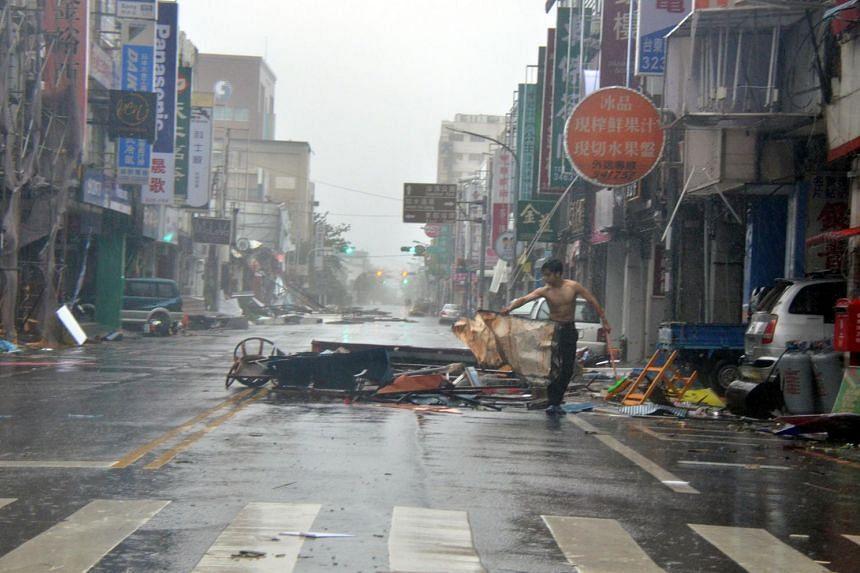 A man holds onto debris in front of a row of shop fronts damaged by strong winds of Typhoon Nepartak in Taitung on July 8, 2016