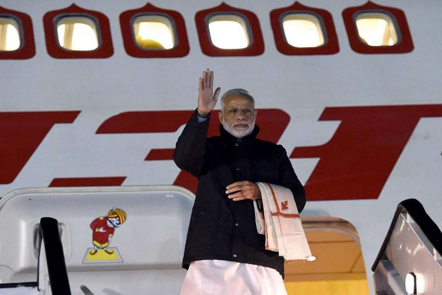 Indian Prime Minister Narendra Modi waves as he arrives at the Waterkloof Air Force Base on the outskirts of Pretoria, South Africa, on July 7, 2016.