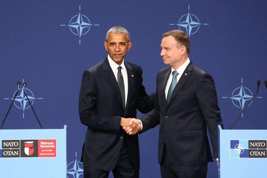 US President Barack Obama (left) and Polish President Andrzej Duda shake hands at a press conference before the Nato Summit in Warsaw, on July 8, 2016.