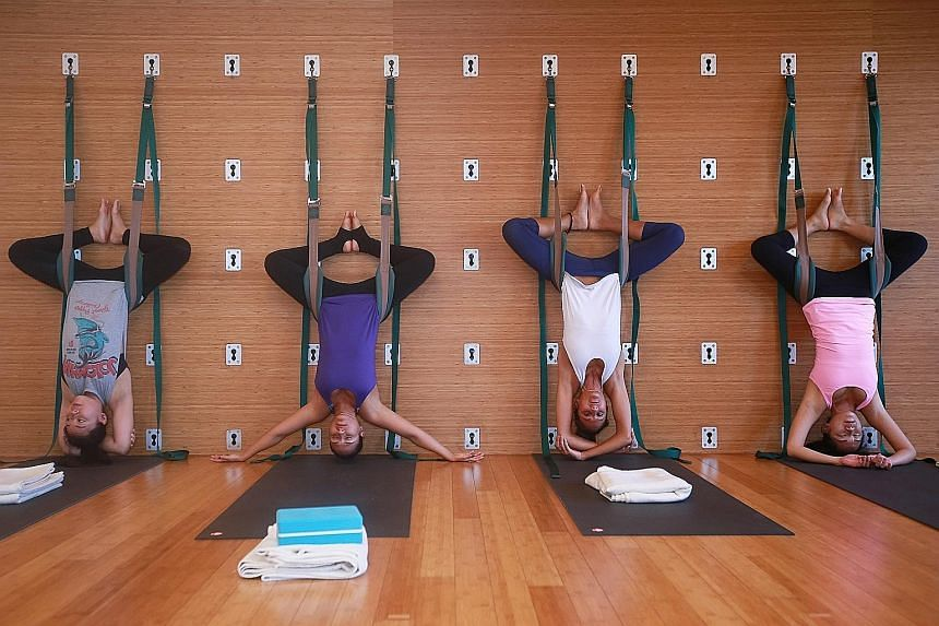 Wall rope yoga allows participants to do a headstand easily with the help of ropes attached to a wall.