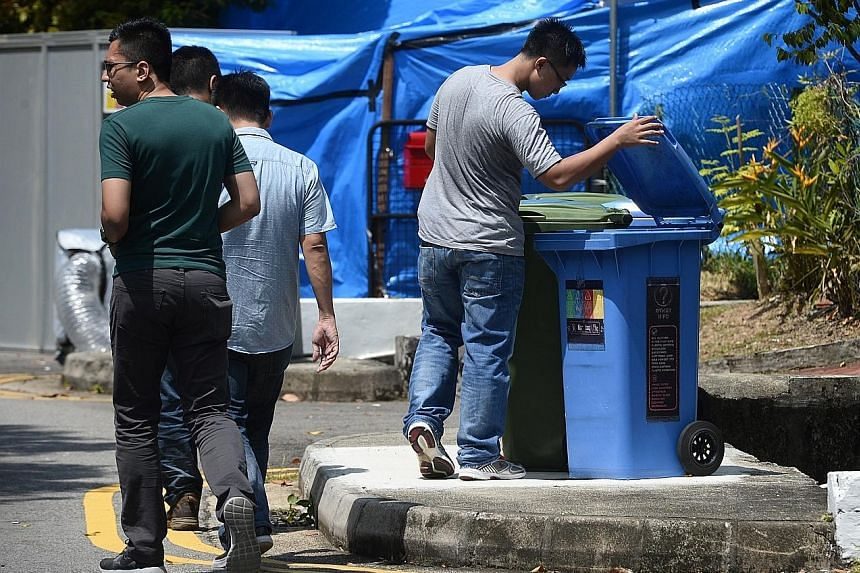 Members of the Singapore Police Force looking for clues in Taman Warna private estate in Holland Village (above) yesterday. They were seen packing up their equipment outside the bank branch (below). The suspect is still at large.