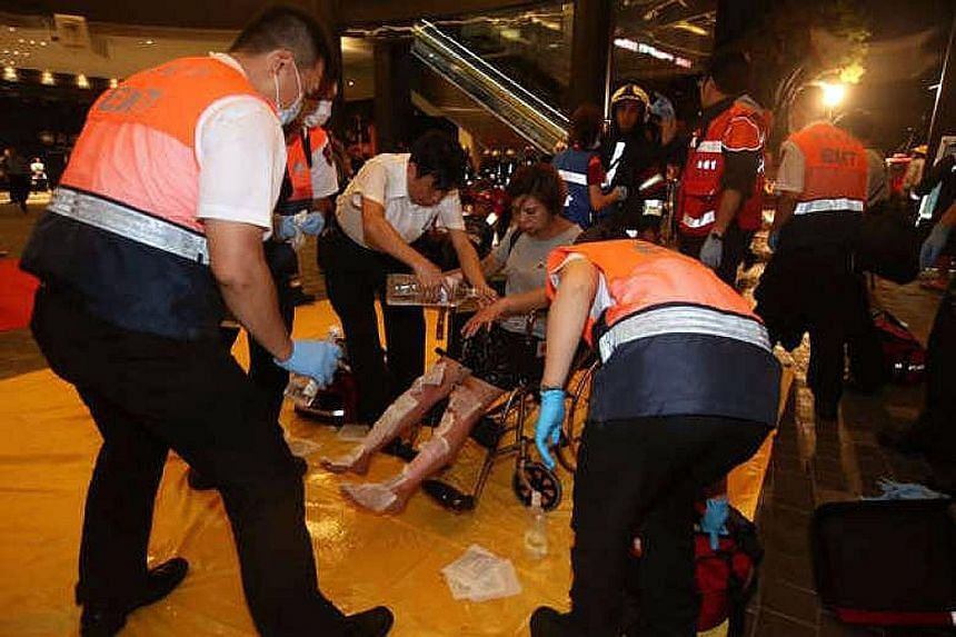 Above: A member of a bomb squad inside the train carriage. Witnesses say they saw a man leaving a bag in the cabin moments before the explosion. Left: Emergency service staff tending to an injured passenger after a blast on board a train in Taipei's