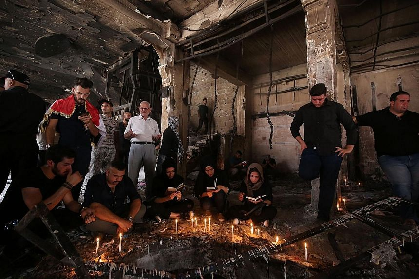 Iraqis praying on Wednesday at the site of a suicide bombing attack which took place on Sunday in Baghdad's Karrada neighbourhood. At least 280 people were killed. Many Iraqis blame their suffering on bad decisions made by the US and Britain.
