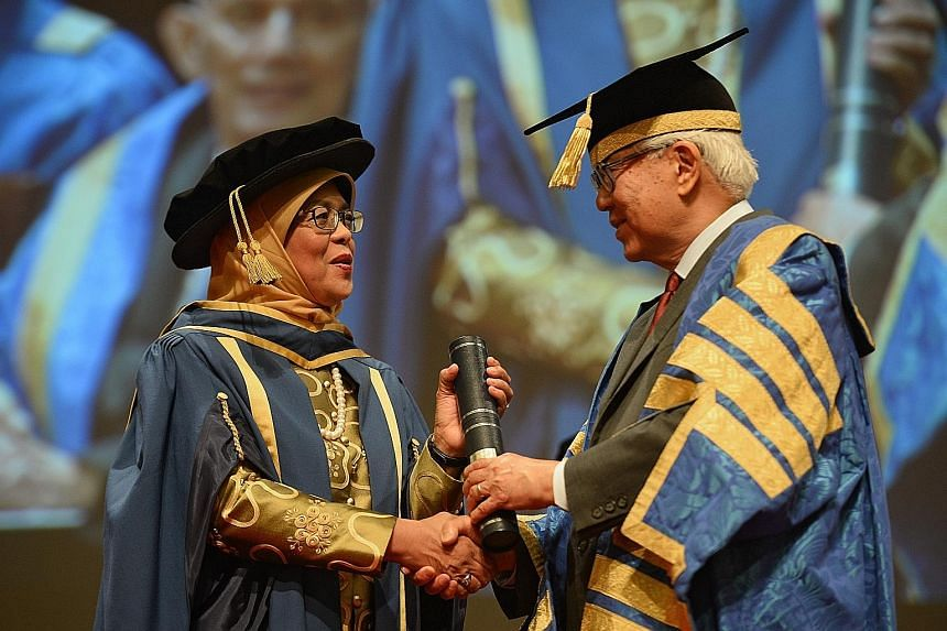 Madam Halimah receiving her scroll from President Tan, who is also NUS chancellor, during a ceremony at NUS yesterday. The accolade puts her among luminaries such as founding Prime Minister Lee Kuan Yew.