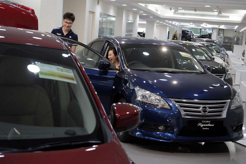 Customers look at cars at the Nissan car showroom in Leng Kee Road on Jan 6.