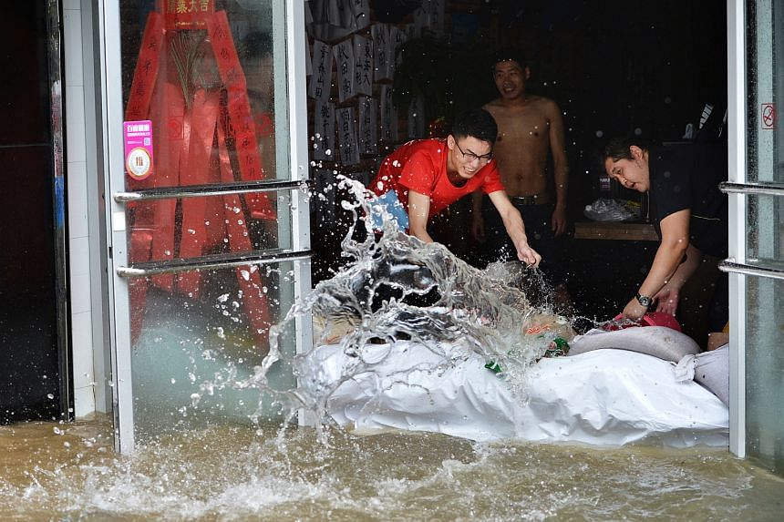 People remove flooded water from a restaurant in Wuhan, Hubei province, China, July 6.