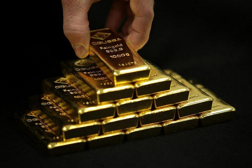 An employee arranges gold bars for a posed photograph. Japanese investors are buying gold to store in Switzerland.