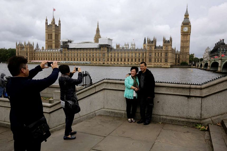 Chinese tourists take pictures near the Big Ben clock tower in London, on June 29, 2016.