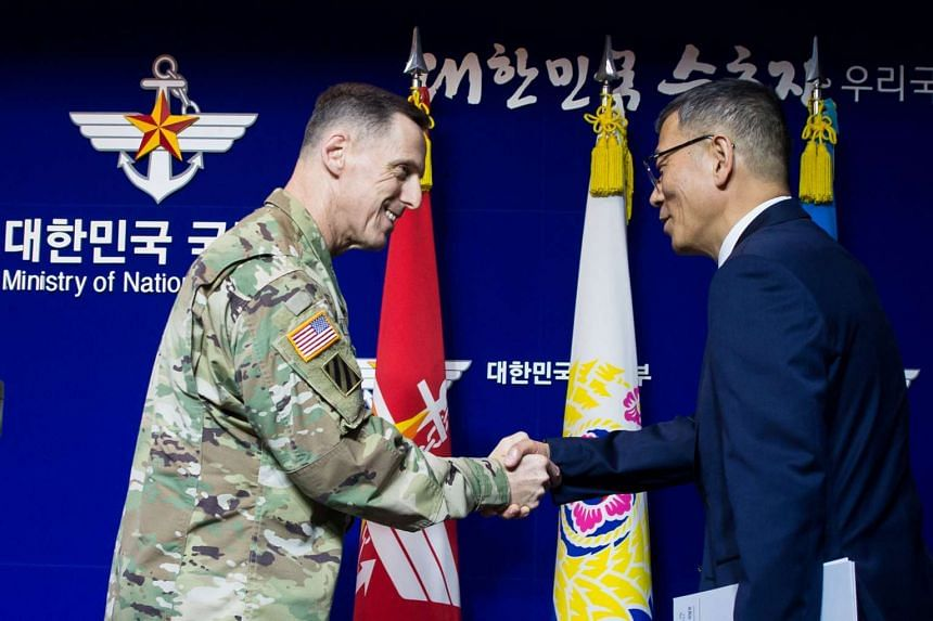 South Korean Defence Ministry's Deputy Minister (right) shakes hands with the commander of US Forces Korea's Eighth Army Lieutenant General at a news conference about deploying Thaad.