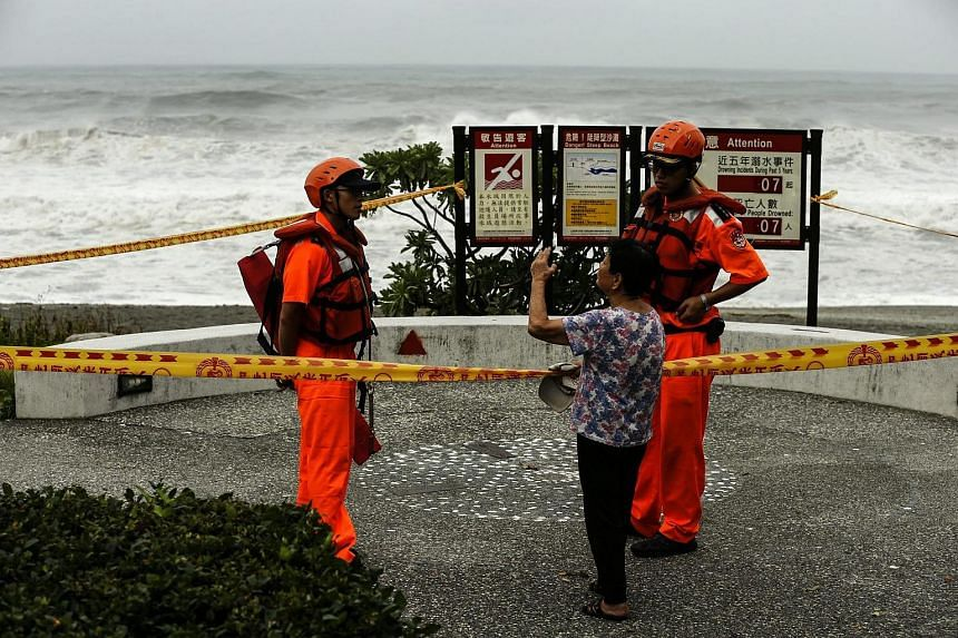 Taiwanese coast guards secure a perimeter at the coastline as typhoon Nepartak moves towards the shoreline of Yilan, Taiwan, on July 7.
